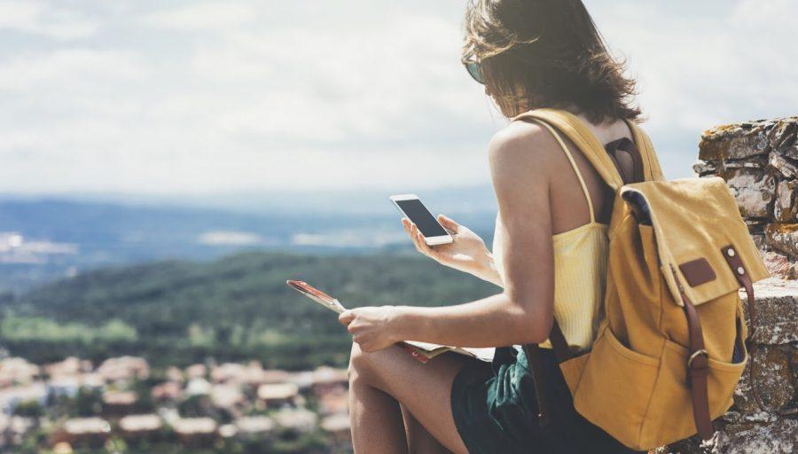 Nainen istumassa vuorenrinteellä kartta ja kännykkä kädessä.
