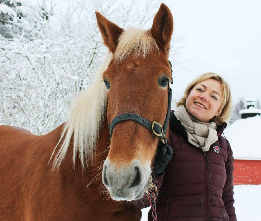 Henna Virkkunen ja hevonen talvimaisemassa.