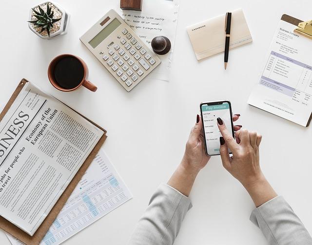 Naisen käsi selaamassa kännykkää. Ympärillä sanomalehti, laskin, kahvikuppi ja muuta sekalaista toimistotavaraa.