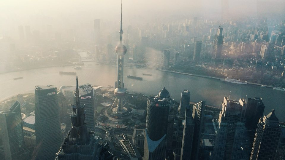 Shanghain sumuista keskustaa. Etualalla pilvenpiirtäjiä, taustalla joki.