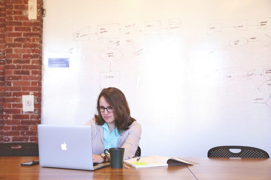 Nainen kannettavan tietokoneen kanssa. Taustalla iso piirtotaulu, johon on piirretty erilaisia kaavioita.