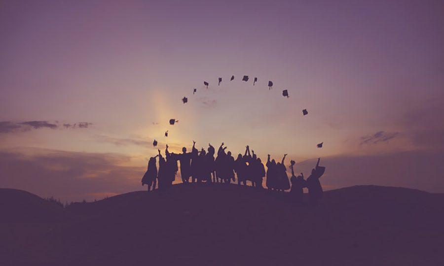 Ryhmä yliopisto-opiskelijoita heittämässä hattunsa ilmaan.