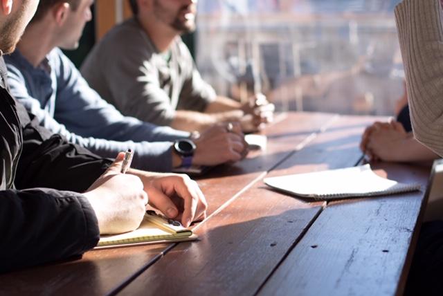 Ryhmä miehiä keskustelemassa pöydän ääressä.