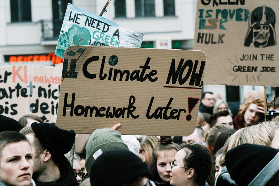 """Mielenosoitus, jossa nuori kantaa kylttiä """"ilmasto nyt, läksyt myöhemmin""""."""