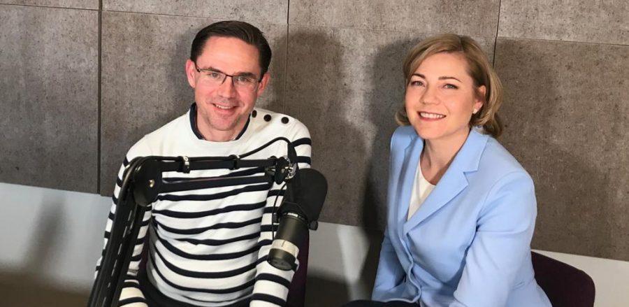 Henna Virkkunen ja Jyrki Katainen äänittämässä podcastia. Etualalla iso mikrofoni.