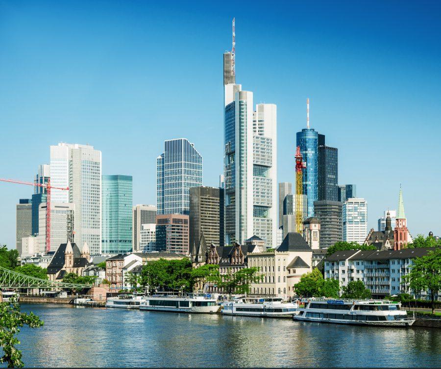 Frankfurtin pilvenpiirtäjiä. Etualalla joki ja vanhoja kivitaloja.