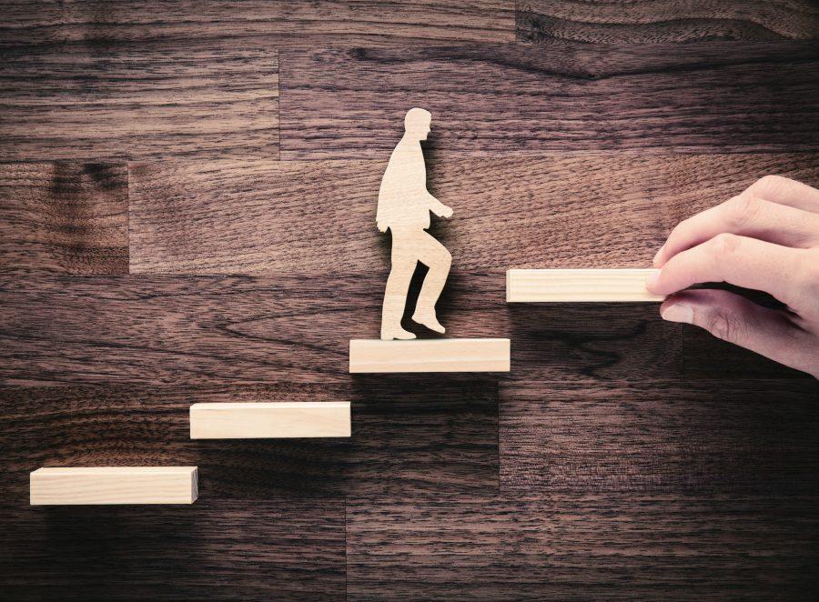 Puuseinää vasten aseteltu puukuvio, jossa mies kiipeää portaita.