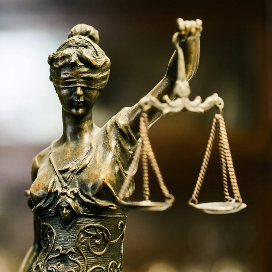 Metallinen lakia kuvaava patsas, jossa vaakaa kannatteleva nainen silmät sidottuina.