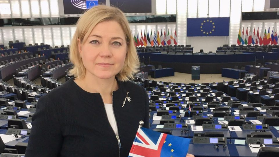 Henna Virkkunen parlamentin täysistuntosalissa lipun kanssa, joka on puoliksi EU:n lippu ja puoliksi Ison-Britannian lippu.