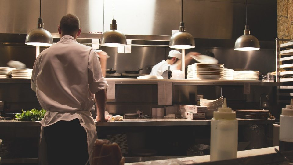 Kokkeja laittamassa ruokaa suuressa keittiössä.