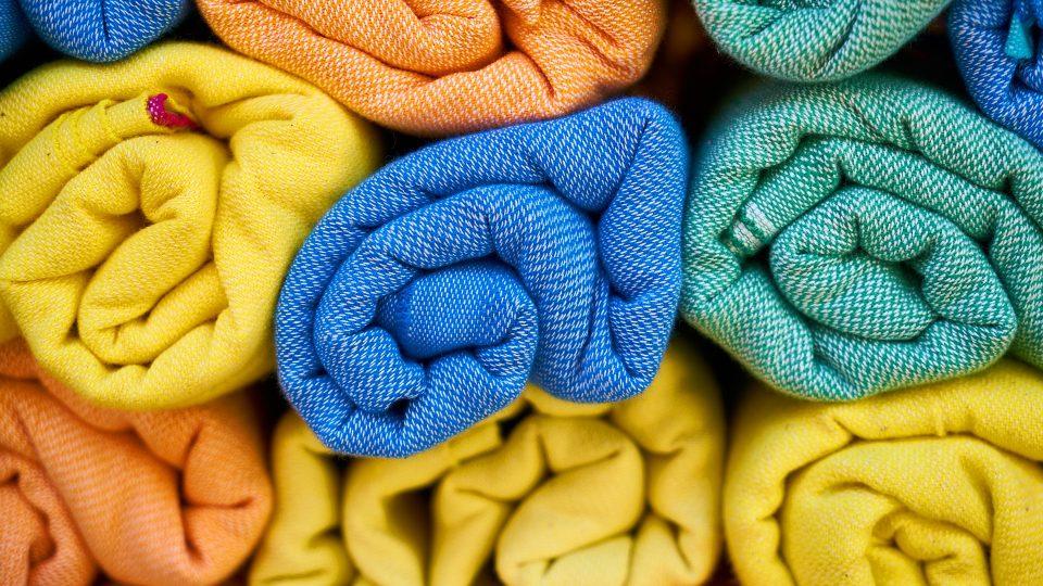 Erivärisiä pyyhkeitä pinottuna.