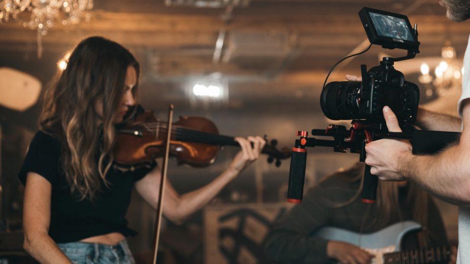 Nainen soittamassa viulua. Etualalla mies kuvaamassa soittoa videokameralla.