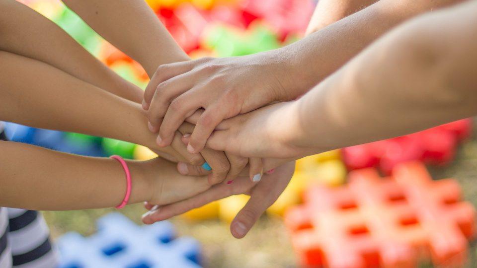 Ryhmä nuoria laittamassa kädet yhteen.