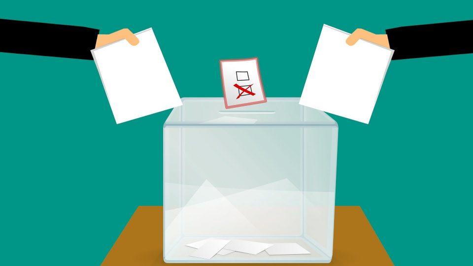 Kaksi kättä laittamassa vaalilipuketta uurnaan.