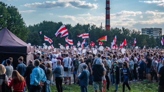 Mielenosoittajia heiluttamassa Valko-Venäjän punavalkoisia lippuja.