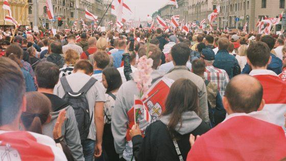 Valkovenäläisiä mielenosoittajia Valko-Venäjän punavalkoisten lippujen kanssa marssimassa Minskin kaduilla.