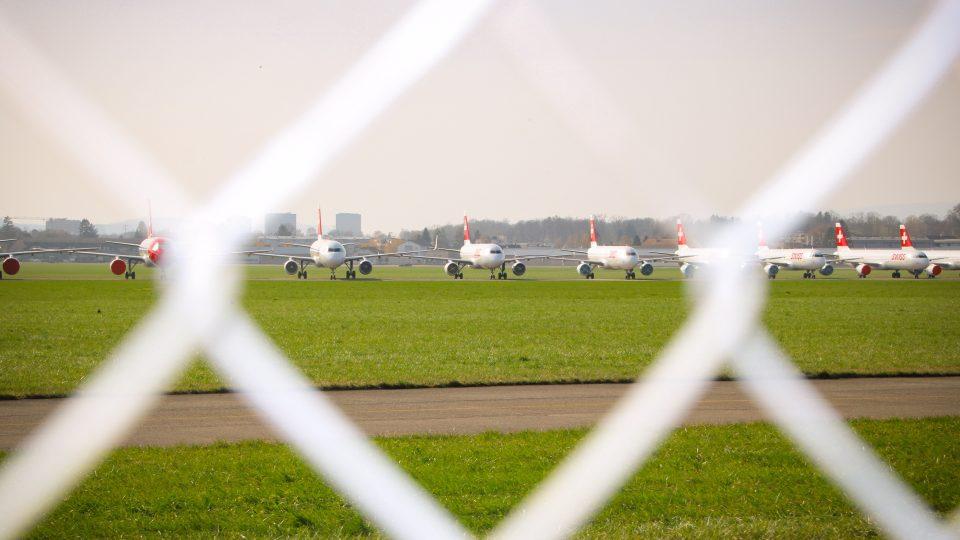 Pysäköityjä lentokoneita verkkoaidan läpi kuvattuna.