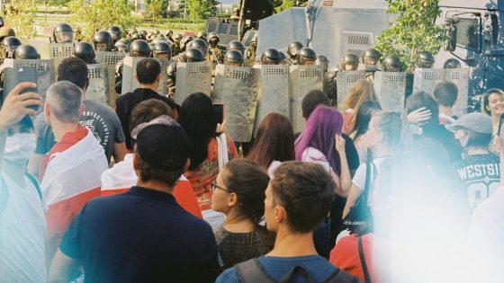 Valkovenäläisiä mellakkapoliiseja kilpien kanssa. Edessä nuoria mielenosoittajia.