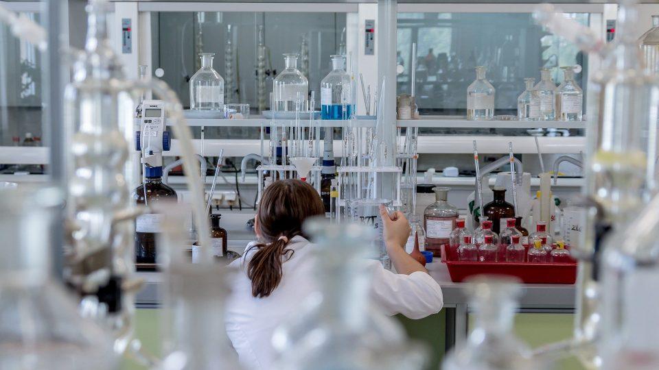 Naistutkija laboratoriossa erilaisten pullojen ja mitta-astioiden keskellä