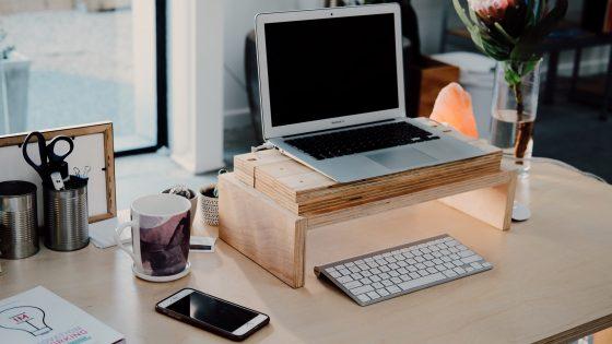 Työpiste, jossa kannettava tietokone, kännykkä ja sekalaisia toimistotarvikkeita.