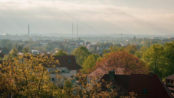 Puita ja talojen kattoja mäenrinteeltä katsottuna. Taustalla savupiippuja.