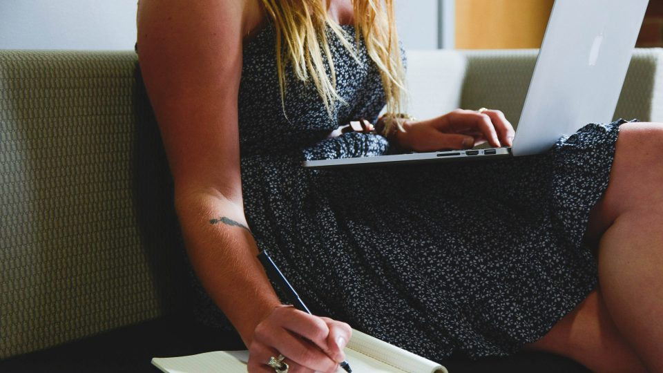 A woman sitting with a laptop and writing on a notepad.