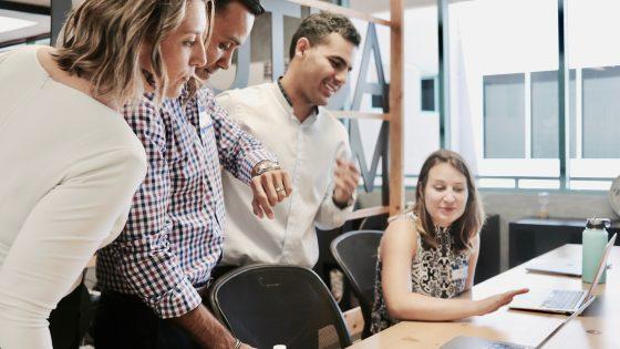 Ryhmä ihmisiä puhumassa tietokoneen äärellä.